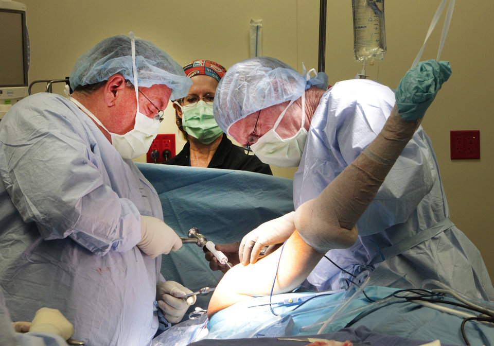 Photo - Physician assistant Gene Fountain and Dr. David Holden perform a rotator cuff surgery at McBride Orthopedic Hospital in Oklahoma City.  David McDaniel - The Oklahoman