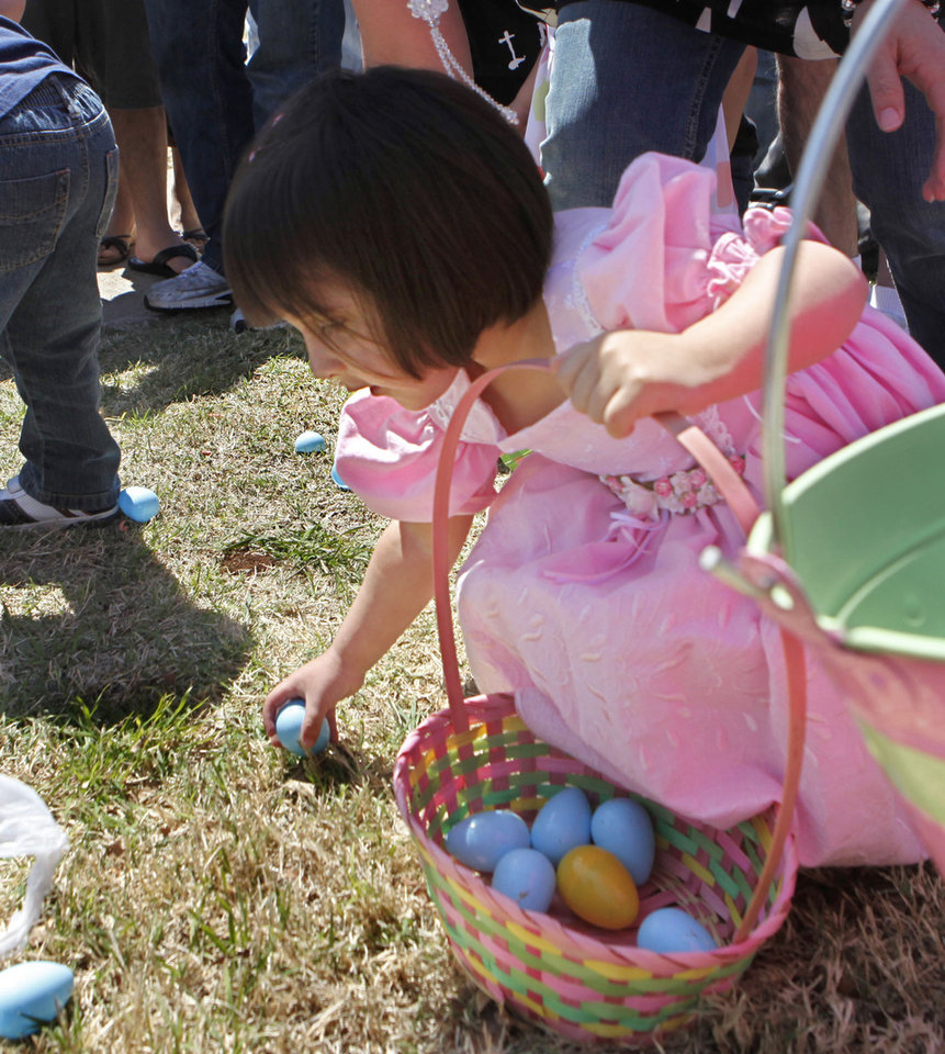 Photo - Two-year-old Emily Vasquez picks up eggs during the  University of Central Oklahoma's Easter Egg Hunt on the UCO campus in Edmond, OK, Saturday, April 3, 2010. By Paul Hellstern, The Oklahoman