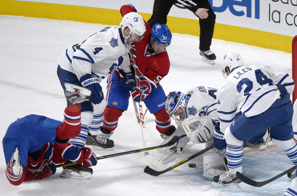 Toronto Maple Leafs goaltender James Reimer, second from right, makes a save against Montreal Canadiens' Brendan Gallagher, left, as Leafs' Cody Franson (4) and John-Michael Liles (24) and Canadiens' David Desharnais (51) look for a rebound during the second period of an NHL hockey game in Montreal, Saturday, Feb. 9, 2013. (AP Photo/The Canadian Press, Graham Hughes)
