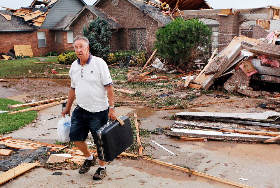 Photo - Jim walks up his driveway carrying a suitcase and a plastic bag with a few items he retrieved from his  home on the Cedar Valley East Golf Course in Guthrie after a tornado destroyed or damaged numerous homes on his street lateTuesday afternoon,  May 24, 2011,   Photo by Jim Beckel, The Oklahoman
