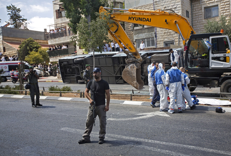 Photo - Israeli police officers stand guard at the scene of an attack in Jerusalem, Monday, Aug. 4, 2014. An Israeli-declared cease-fire and troop withdrawals slowed violence in the Gaza war Monday, though an attack on Israeli bus that killed one person in Jerusalem underscored the tensions still simmering in the region. (AP Photo/Sebastian Scheiner)