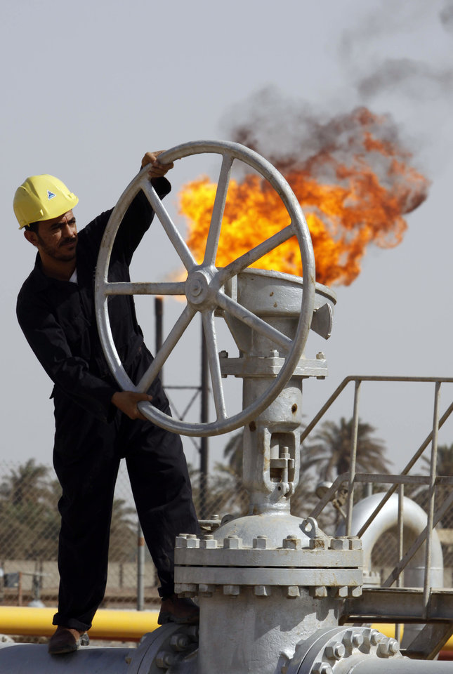 FILE - In this file photo of Friday, July 17, 2009, an Iraqi worker operates valves at the Nahran Omar oil refinery near the city of Basra, 340 miles (550 kilometers) southeast of Baghdad, Iraq. The International Energy Agency predicted Tuesday Oct. 9, 2012 that Iraq will consolidate its position as a global oil power _ allowing it to rebuild the economy of a nation ravaged by war and decades of Saddam Hussein�s autocratic rule. The leading global energy monitor reported that Iraq�s annual revenues from energy exports could double to an average of $200 billion annually over the next 20 years. That optimistic scenario would make Iraq�s economy the same size as that of Saudi Arabia now by 2035. (AP Photo/Nabil al-Jurani, File)