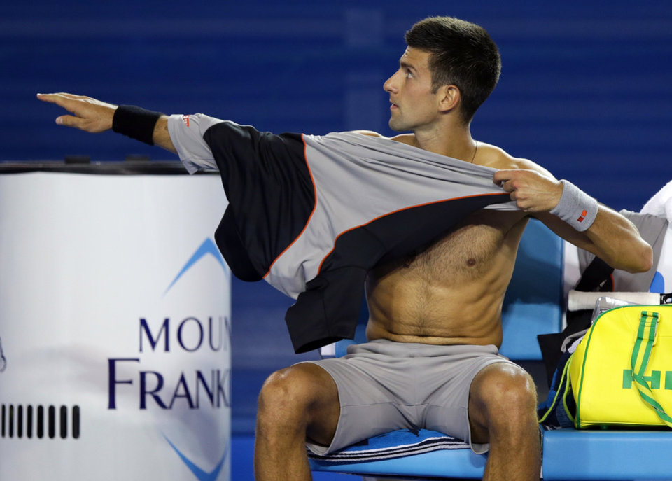 Photo - Novak Djokovic of Serbia changes his shirt between games as he plays Denis Istomin of Uzbekistan during their third round match at the Australian Open tennis championship in Melbourne, Australia, Friday, Jan. 17, 2014.(AP Photo/Aaron Favila)