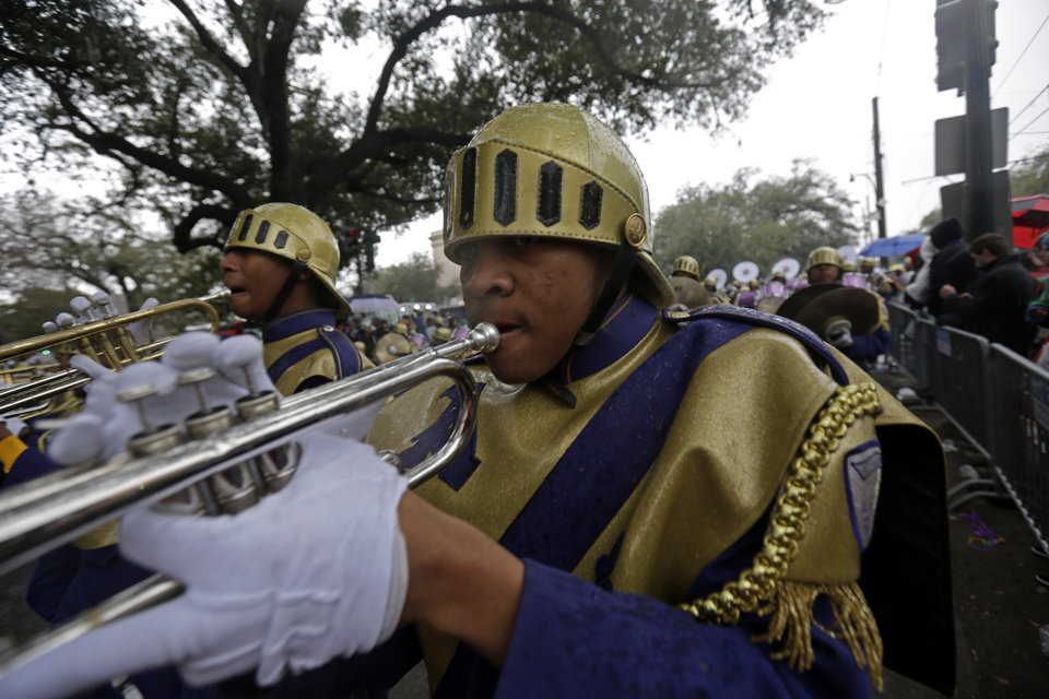 Photo - Members of the St. Augustine High Marching 100 band march in the Krewe of Zulu parade during Mardi Gras day in New Orleans, Tuesday, March 4, 2014. The Zulu parade began on schedule, led by a New Orleans police vanguard on horseback that included Mayor Mitch Landrieu.(AP Photo/Gerald Herbert)