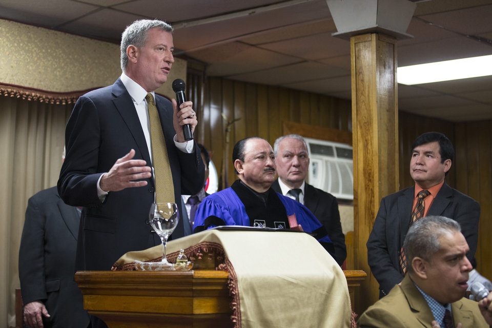 Photo - New York Mayor Bill de Blasio speaks during Sunday services at the Church of God of Third Avenue as the congregation welcomed members of the Spanish Christian Church that was destroyed by Wednesday's explosion in the East Harlem neighborhood of New York, Sunday, March 16, 2014. The Spanish Christian Church had been located on the first floor of one of the destroyed buildings. On Saturday a crew at the blast site found a large Bible in the rubble and returned it to the church's pastor. (AP Photo/John Minchillo)