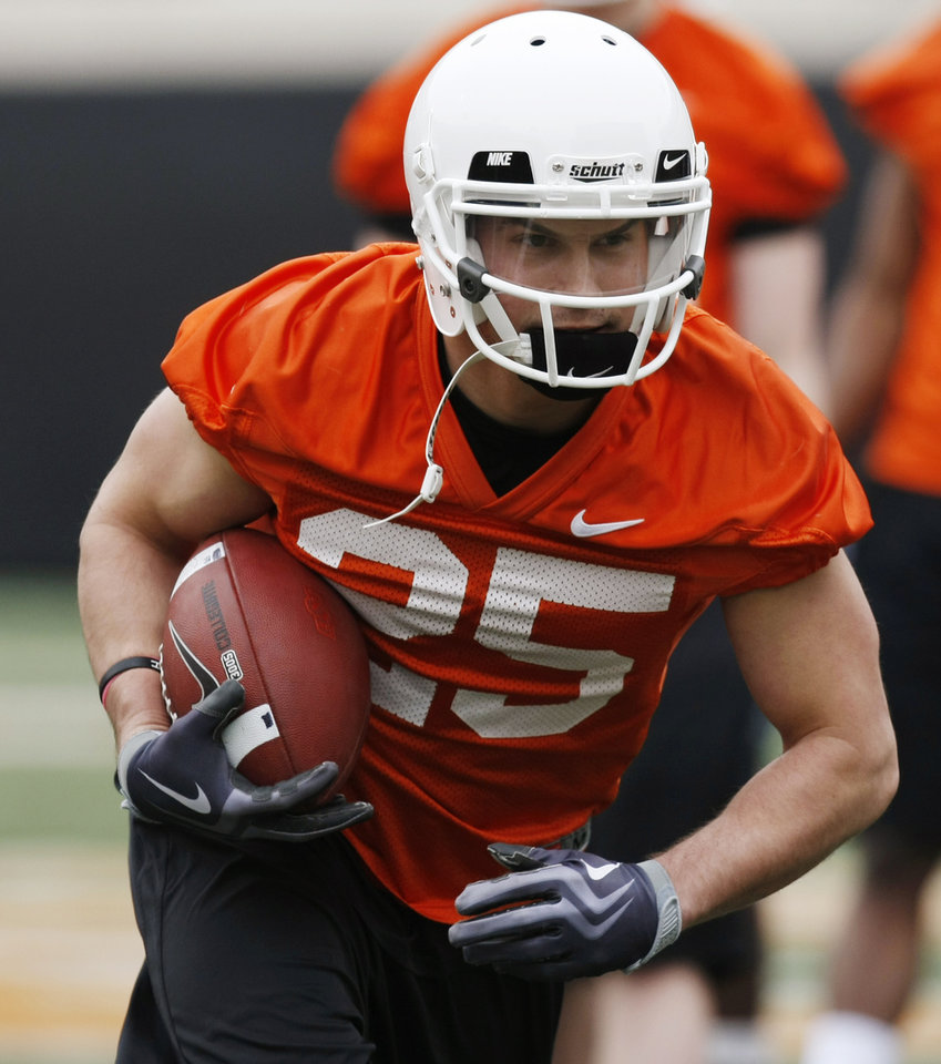 Photo - OSU's Josh Cooper (25) runs after a catch during Oklahoma State spring football practice at Boone Pickens Stadium in Stillwater, Okla., Monday, March 7, 2011. Photo by Nate Billings, The Oklahoman