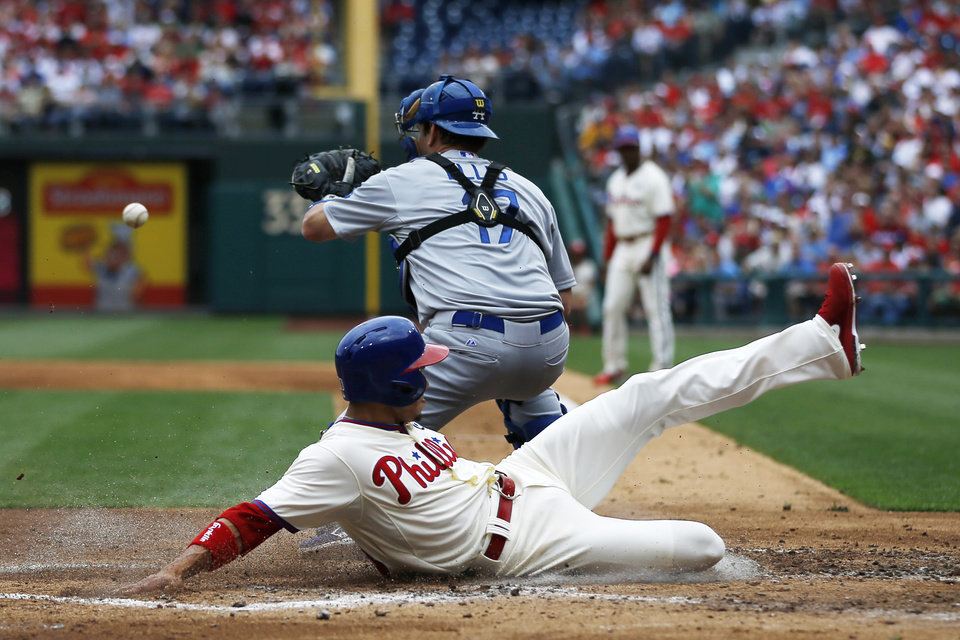 Photo - Philadelphia Phillies' Cesar Hernandez, bottom, scores past Los Angeles Dodgers catcher A.J. Ellis on a single by Ben Revere during the second inning of a baseball game, Saturday, May 24, 2014, in Philadelphia. (AP Photo/Matt Slocum)