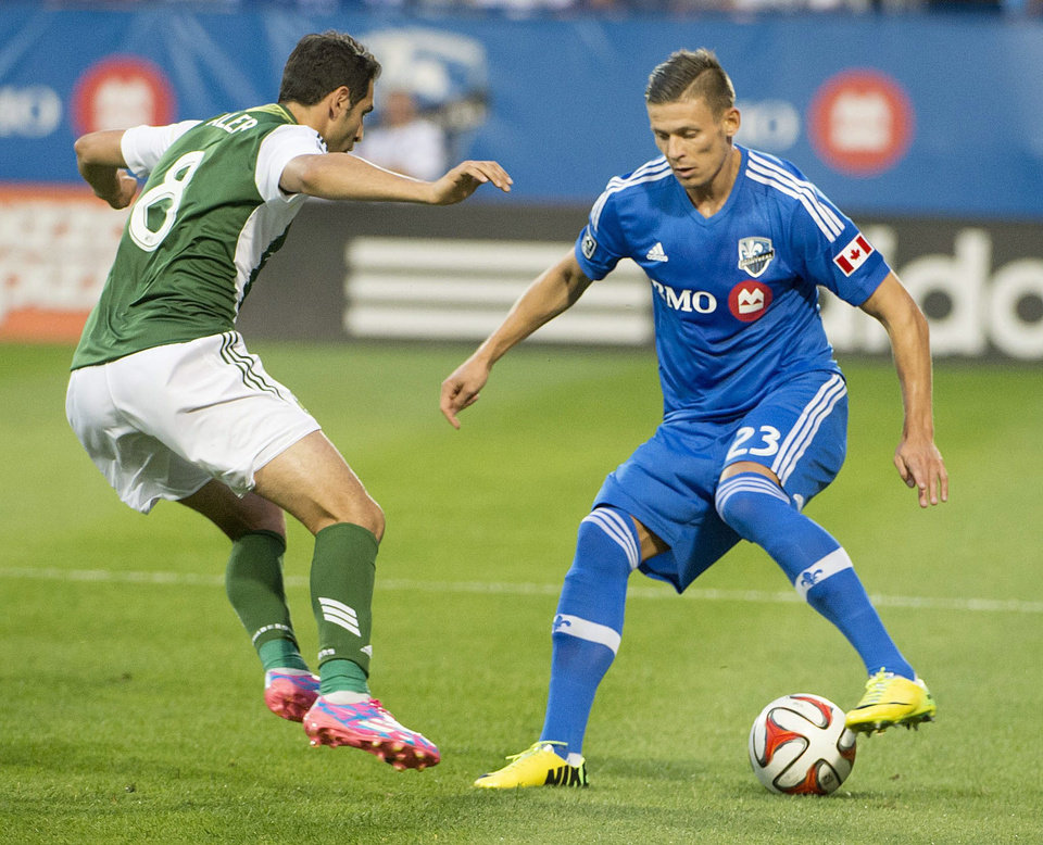 Photo - Montreal Impact's Krzysztof Krol controls the ball in front of Portland Timbers' Diego Valeri during the first half of an MLS soccer game Sunday, July 27, 2014, in Montreal. (AP Photo/The Canadian Press, Peter McCabe)
