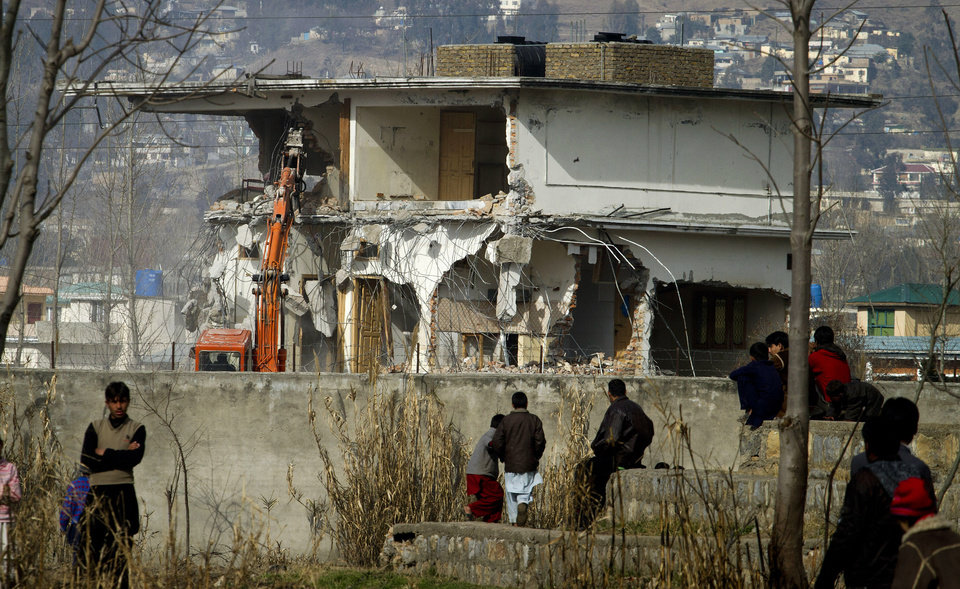 Photo -   Local residents watch as authorities use heavy machinery to demolish the compound of Osama bin Laden in Abbottabad, Pakistan on Sunday, Feb. 26, 2012. Pakistan was more than halfway done Sunday demolishing the three-story compound where bin Laden was killed by U.S. commandos last May, erasing a concrete reminder of a painful and embarrassing chapter in the country's history. (AP Photo/Anjum Naveed)