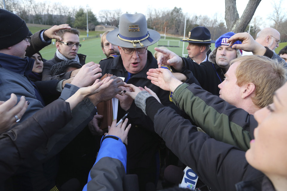 Photo - Lt. J. Paul Vance of the Connecticut State Police is surrounded by reporters as he hands out the list of victims of the shooting at the Sandy Hook Elementary School,  Saturday, Dec. 15, 2012 in Sandy Hook village of Newtown, Conn.  The victims of the shooting were shot multiple times by semiautomatic rifle, according to Connecticut Chief Medical Examiner  H. Wayne Carver II, M.D.  Carver called the injuries