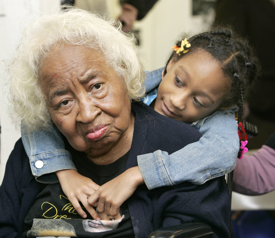 Photo - Civil rights pioneer Clara Luper gets a hug from 9 year-old Alexia Grant during a watch party of the Inauguration of President Barack Obama. Luper was watching TV at the Freedom Center at NE 26th and Martin Luther King Blvd. in Oklahoma City. January  20, 2009.  BY STEVE GOOCH, THE  OKLAHOMAN.