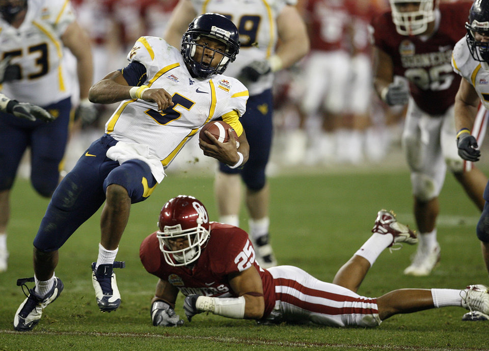Photo - West Virginia's Patrick White (5) gets past Oklahoma's D.J. Wolfe (25) during the second half of the Fiesta Bowl college football game between the University of Oklahoma Sooners (OU) and the West Virginia University Mountaineers (WVU) at The University of Phoenix Stadium on Wednesday, Jan. 2, 2008, in Glendale, Ariz. 