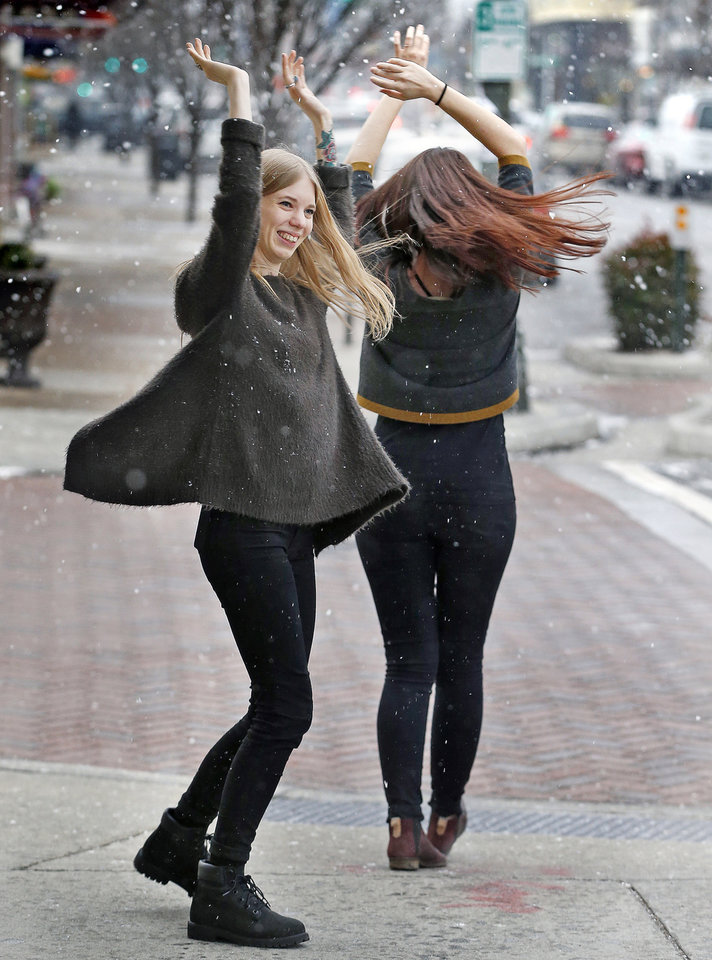 Photo - Mina Douglas, left and Holly Hiday dance in circles to celebrate the snow fall over Carytown outside Need Supply Co. where they work in Richmond, Va. Tuesday, Jan. 21, 2014. Hiday is the store manager.  (AP Photo/Richmond Times-Dispatch, Alexa Welch Edlund)