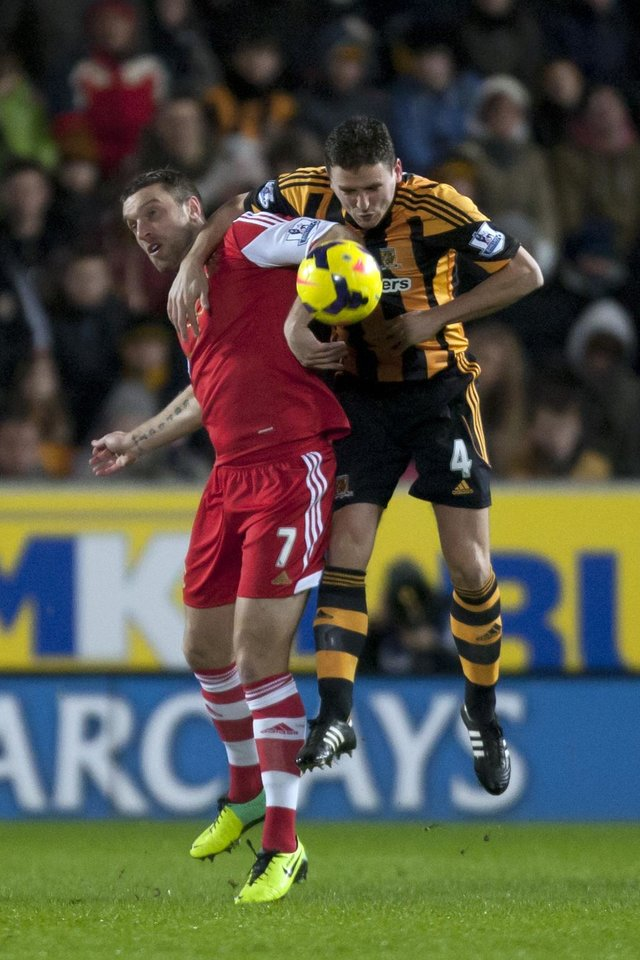 Photo - Hull City's Alex Bruce, right, fights for the ball against Southampton's Rickie Lambert during their English Premier League soccer match at the KC Stadium, Hull, England, Tuesday Feb. 11, 2014. (AP Photo/Jon Super)