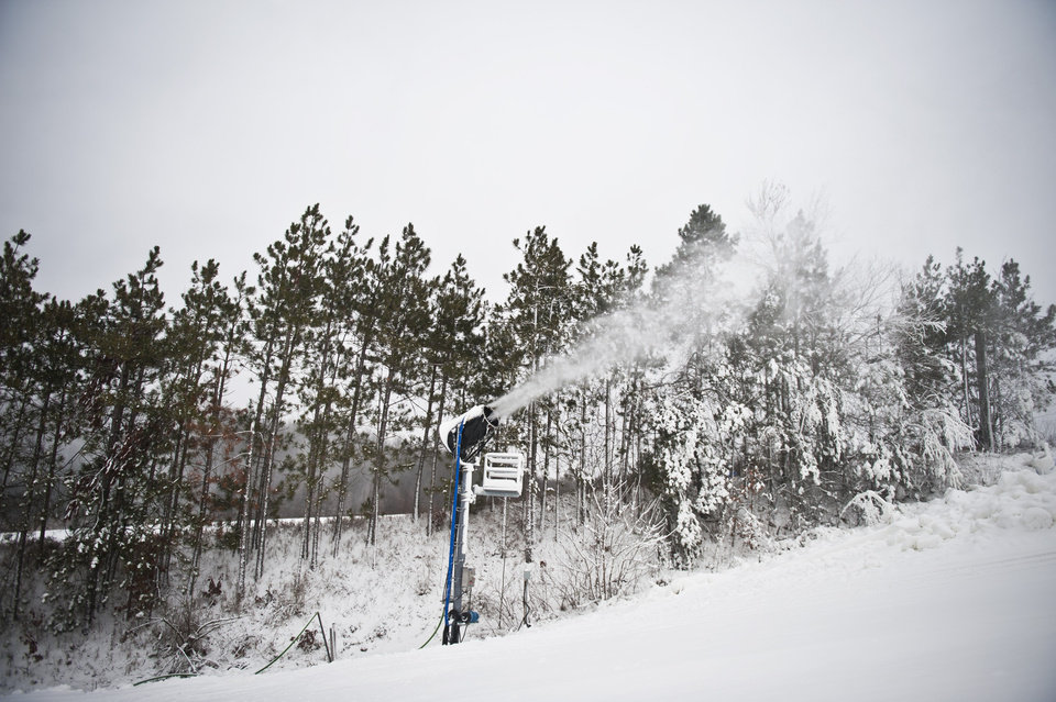 Photo - Snow blowers funnel snow onto Cannonsburg's main runs during Cannonsburg Ski Hill's opening day on Wednesday, Dec. 26, 2012 in Belmont, Mich. (AP Photo/The Grand Rapids Press, Matthew Busch)