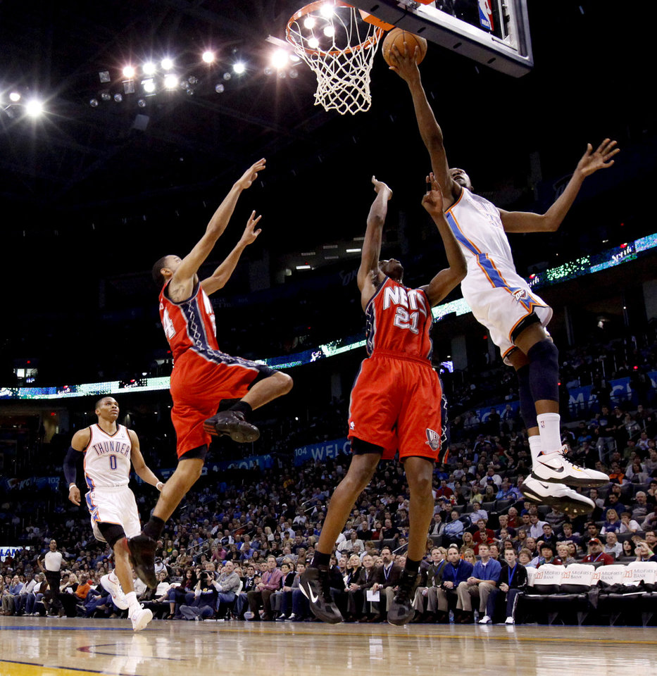 Oklahoma City's Kevin Durant shoots the ball beside New Jersey's Devin Harris, left, and Travis Outlaw as Russell Westbrook watches during the NBA basketball game between the Oklahoma City Thunder and the New Jersey Nets at the Oklahoma City Arena, Wednesday, Dec. 29, 2010.  Photo by Bryan Terry, The Oklahoman