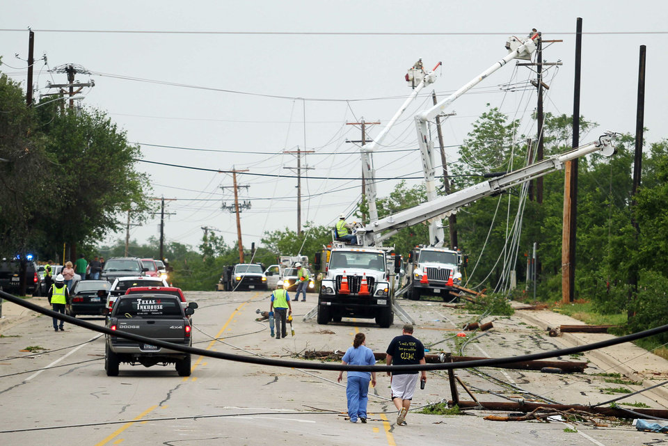 Photo - Crews work to clear power lines damaged by Wednesday's tornado in Cleburne, Texas on Thursday, May 16, 2013. Ten tornadoes touched down in several small communities in Texas overnight, leaving at least six people dead, dozens injured and hundreds homeless. Emergency responders were still searching for missing people Thursday afternoon. (AP Photo/Ron Russek II)