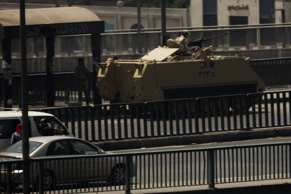Photo - An Egyptian army armored vehicle is seen on a bridge over the Nile river at Zamalek District in Cairo, Egypt, Saturday, Aug. 17, 2013. Authorities say police in Cairo are negotiating with people barricaded in a mosque and promising them safe passage if they leave. Muslim Brotherhood supporters of Egypt's ousted Islamist president are vowing to defy a state of emergency with new protests today, adding to the tension. (AP Photo/Manu Brabo)
