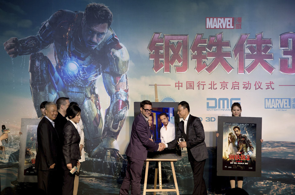 Photo - U.S. actor Robert Downey Jr. center, shakes hands with Chinese actor Wang Xueqi after a photo session during a world premiere event of his new movie