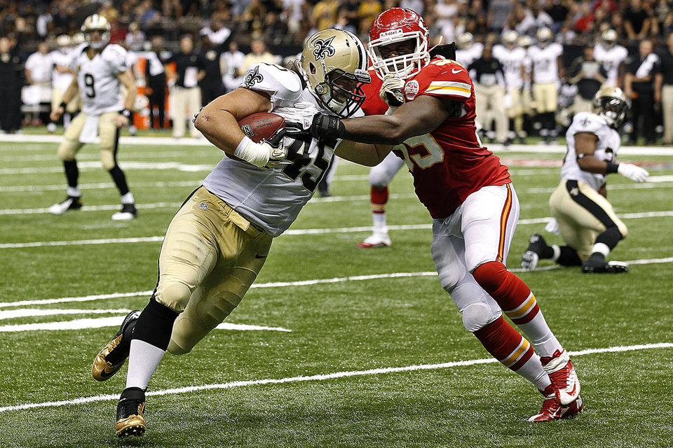Photo -   New Orleans Saints running back Jed Collins (45) scores a touchdown as Kansas City Chiefs inside linebacker Jovan Belcher (59) covers in the second half of an NFL football game in New Orleans, Sunday, Sept. 23, 2012. (AP Photo/Bill Haber)