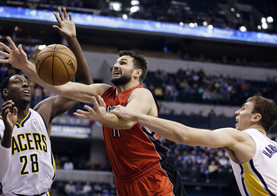 Toronto Raptors\' Linas Kleiza (11) shoots under pressure from Indiana Pacers\' Ian Mahinmi (28) and Tyler Hansbrough during the first half of an NBA basketball game, Tuesday, Nov. 13, 2012, in Indianapolis. (AP Photo/Darron Cummings)