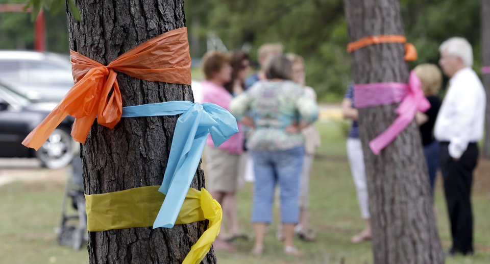 Photo - Faculty and parents gather outside Lemm Elementary School after placing ribbons on the trees in honor of those killed in a multiple shooting Thursday, July 10, 2014, in Spring, Texas. Some of the victims were students at the school. The Harris County Sheriff's Office says Ronald Lee Haskell was booked Thursday on a capital murder/multiple murders charge and held without bond. Authorities believe Haskell fatally shot two adults and four children on Wednesday night and critically wounded a 15-year-old girl, who called 911.(AP Photo/David J. Phillip)