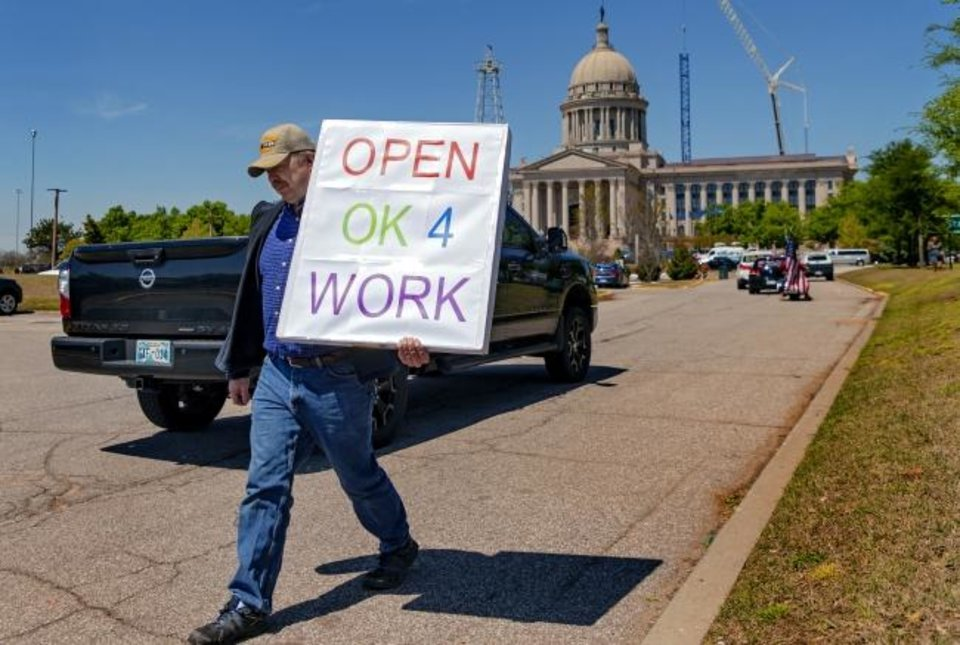 Photo -  Bryan Hall carries his sign as he walks along drivers during the Let's Get Oklahoma Open For Business rally at the Oklahoma State Capitol in Oklahoma City, Okla. on Wednesday, April 15, 2020. Participants gathered to protest the hardship Oklahoma citizens are being placed in due to businesses being forced to close during the COVID-19 pandemic.  [Chris Landsberger/The Oklahoman]