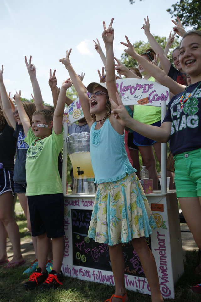 Vivienne Harr, 9, of Fairfax, Calif., and members of the Shawnee community gather around her Make A Stand lemonade stand on Friday. Photo by Aliki Dyer, The Oklahoman <strong>Aliki Dyer - The Oklahoman</strong>