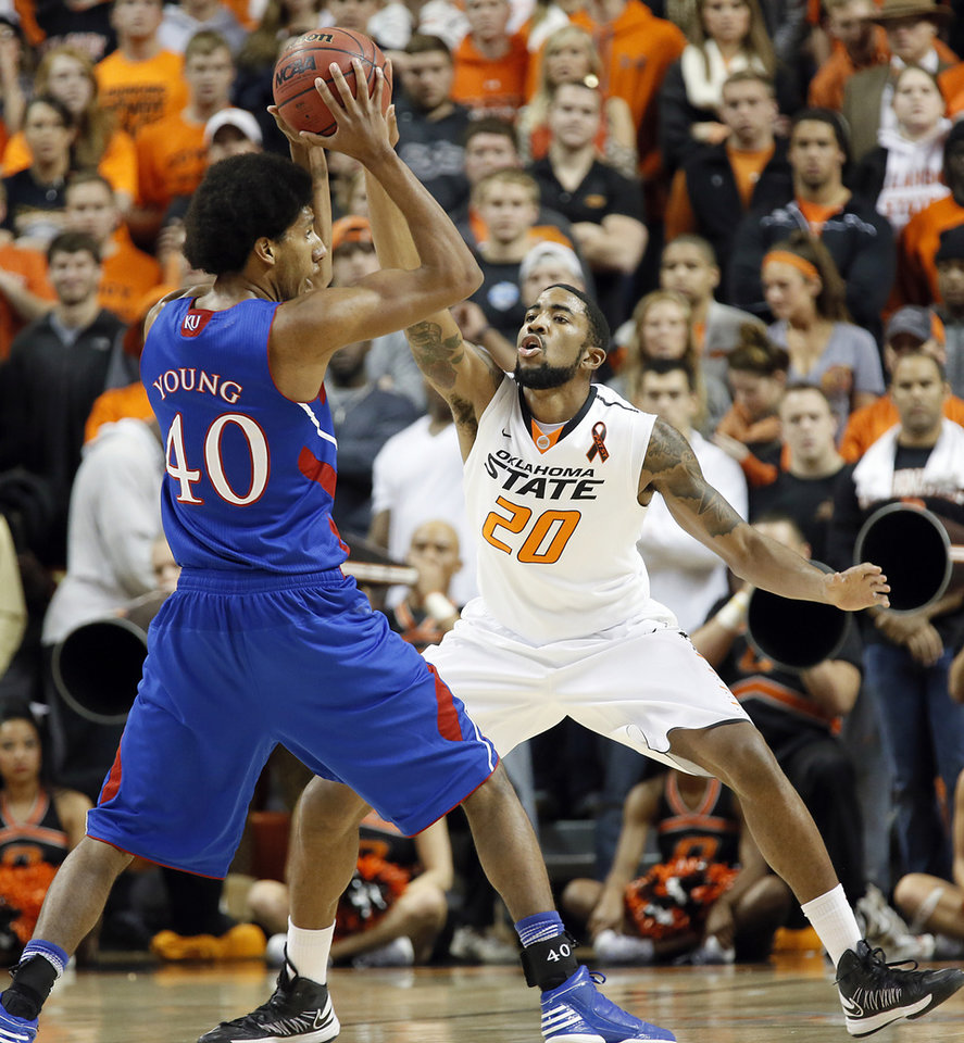 Photo - Oklahoma State 's Michael Cobbins (20) defends on Kansas' Kevin Young (40) during the college basketball game between the Oklahoma State University Cowboys (OSU) and the University of Kanas Jayhawks (KU) at Gallagher-Iba Arena on Wednesday, Feb. 20, 2013, in Stillwater, Okla. Photo by Chris Landsberger, The Oklahoman