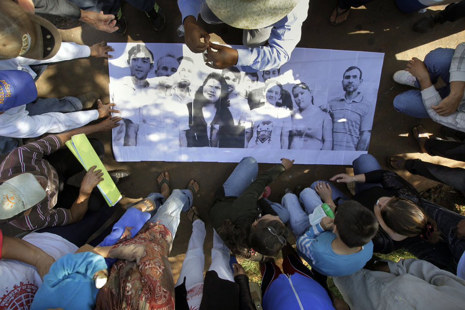 "In this Nov. 15, 2012 photo, farmers prepare a banner with pictures of landless farmers, some of whom were arrested during clashes with police, as they prepare to march to demand their release at the Yvy Pyta settlement near Curuguaty, Paraguay.  The ""Massacre of Curuguaty"" on June 15 killed 11 farmers and 6 police officers when negotiations between farmers occupying a rich politician's land ended with a barrage of bullets. The underlying dispute that set up the clash was decades in the making. The area's poor residents have long alleged that the land was effectively stolen from the state by Sen. Blas Riquelme, a leader of the Colorado Party that backed dictator Alfredo Stroessner from 1954 to 1989, and has dominated the nation's politics ever since. (AP Photo/Jorge Saenz)"