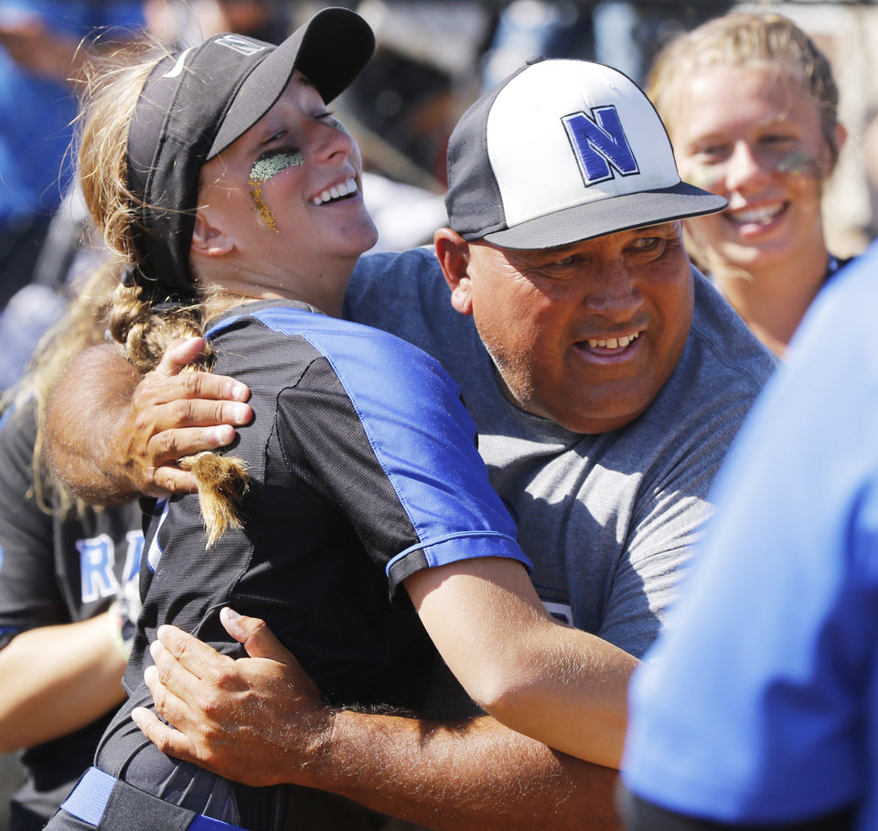 Photo - NHS coach Mike Crossley hugs #7 Emma Strange as she goes to get her medal during the 4A Fast Pitch Championship game between Newcastle and Purcell at the Ball Fields at Firelake in Shawnee, Saturday, October 19, 2019. [Doug Hoke/The Oklahoman]