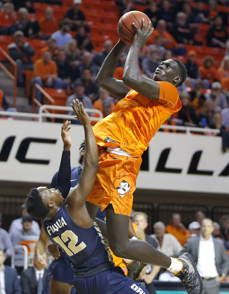 Photo - Oklahoma State's Yor Anei (14) puts up a shot over Oral Roberts' R.J. Fuqua (12) during an NCAA basketball game between the Oklahoma State University Cowboys (OSU) and the Oral Roberts Golden Eagles (ORU) at Gallagher-Iba Arena in Stillwater, Okla., Wednesday, Nov. 6, 2019. [Bryan Terry/The Oklahoman]