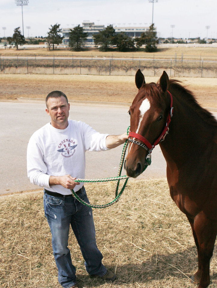 """Photo - Horse trainer Heath Taylor works with """"First Prize Leesa"""" at Remington Park in Oklahoma City on  Friday. Photo BY PAUL HELLSTERN, THE OKLAHOMAN"""