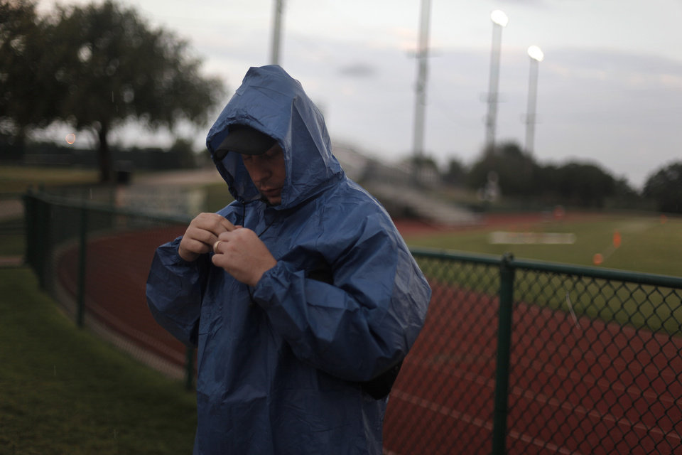 Photo - Mike Millican, of Yukon, puts his rain gear on before a high school football game between Heritage Hall and Clinton in Oklahoma City, Friday, Sept. 7, 2012.  The game was delayed due to lightning.  Photo by Garett Fisbeck, The Oklahoman