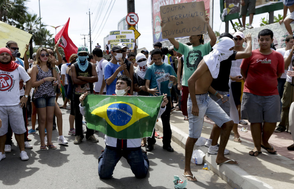 A protester holds a Brazilian flag during a demonstration a few miles from the soccer stadium where Spain and Italy will play in a Confederations Cup semifinal soccer game in Fortaleza, Brazil, Thursday, June 27, 2013. It\'s the latest in a series of massive, nationwide protests that have hit Brazil since June 17. Demonstrators are angered about corruption and poor public services despite a heavy tax burden. Protests are also denouncing the billions of dollars spent to host the World Cup and the 2016 Olympics in Rio - money they say should be going toward better hospitals, schools, transportation projects and schools. (AP Photo/Natacha Pisarenko)
