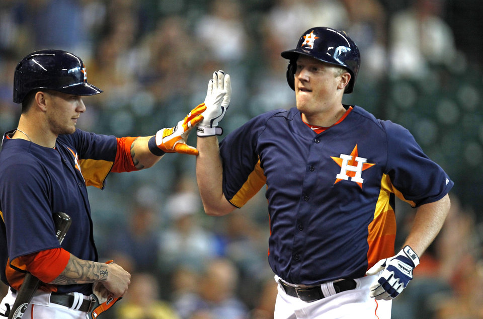 Photo - Houston Astros' Marc Krauss, right, is congratulated by teammate Brandon Barnes after hitting a solo home run in the second inning of a baseball game against the Los Angeles Angels Sunday, Sept. 15, 2013, at Minute Maid Park in Houston. (AP Photo/Eric Christian Smith)