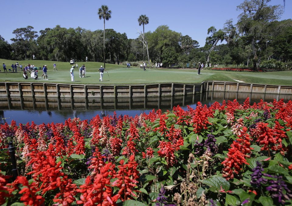 Photo - Players work on their putting on the 13th green during a practice round for The Players championship golf tournament at TPC Sawgrass in Ponte Vedra Beach, Fla., Wednesday, May 7, 2014. (AP Photo/John Raoux)