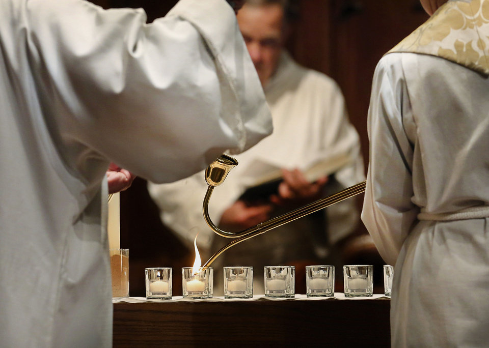 At St. Paul's Episcopal Cathedral in Oklahoma City, 28 small white candles are lit at the beginning of a service remembering those who died as a result of a Connecticut shooting massacre. Photo by Jim Beckel, The Oklahoman