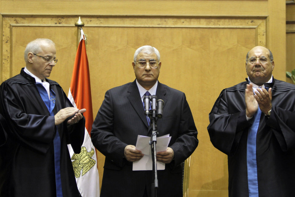 Egypt's chief justice Adly Mansour, center, is applauded by by chiefs of the constitutional court after he is sworn in as the nation's interim president Thursday, July 4, 2013. The chief justice of Egypt's Supreme Constitutional Court was sworn in Thursday as the nation's interim president, taking over hours after the military ousted the Islamist President Mohammed Morsi.(AP Photo/Amr Nabil)