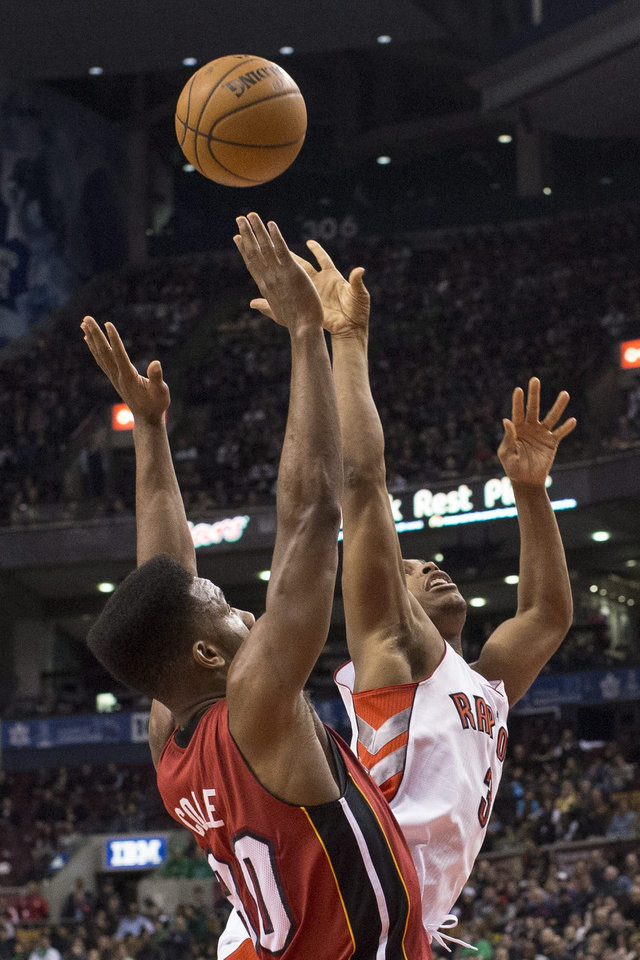 Toronto Raptors' Kyle Lowry, right, battles for the ball with Miami Heat's Norris Cole during first half NBA basketball action in Toronto on Sunday March 17, 2013. (AP Photo/THE CANADIAN PRESS,Chris Young)