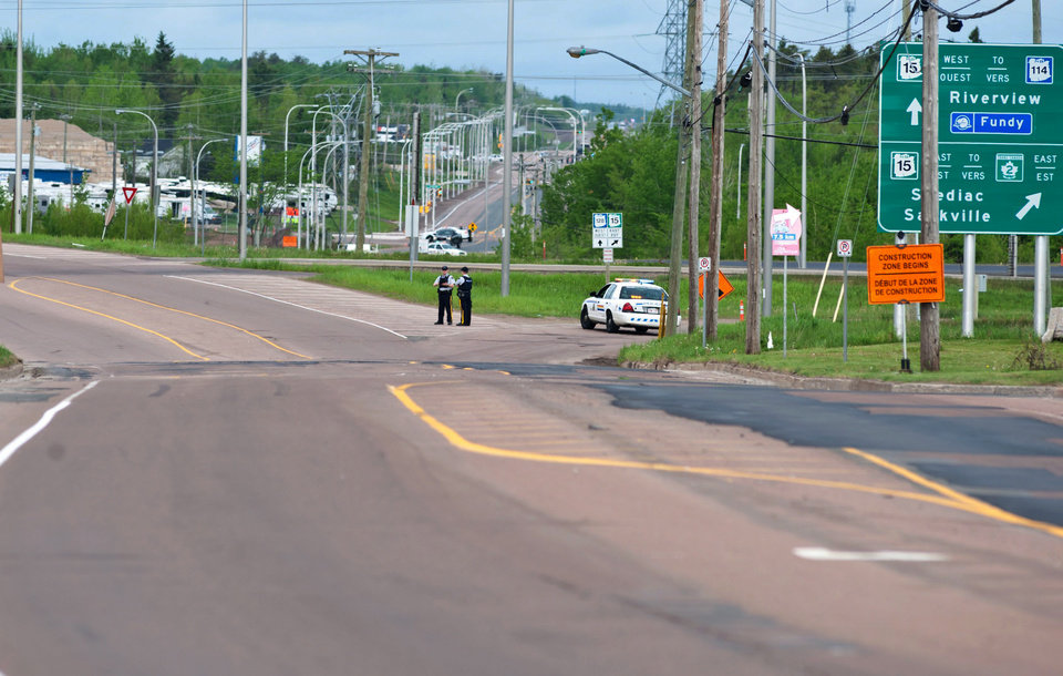 Photo - Royal Canadian Mounted Police block a highway onramp along Berry Mills road in Moncton,  New Brunswick as the RCMP maintains a lockdown in the area on Thursday, June 5, 2014. A RCMP manhunt for a gunman suspected of killing three Mounties and wounding two others passed the 12-hour mark Thursday in Moncton as a large section of the New Brunswick city was under a virtual siege. (AP Photo/The Canadian Press, Marc Grandmaison)