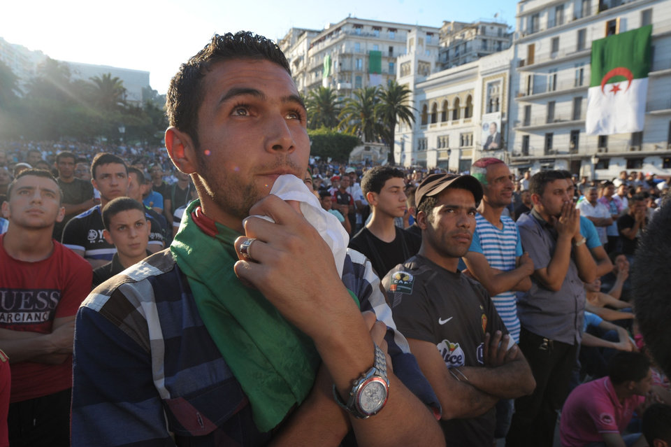 Photo - In this photo dated Tuesday, June 17, 2014, Algerian soccer fans watch their team's World Cup soccer match with Belgium on a large screen set up in Algiers Zocalo June 17, 2014. Belgium defeated Algeria 2-1. (AP Photo/Sidali Djarboub)