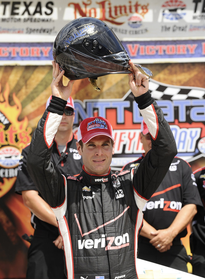 Photo - Will Power, of Australia, holds up the pole position helmet after posting the highest speed to take the pole position during qualifying for the IndyCar auto race at Texas Motor Speedway in Fort Worth, Friday, June 6, 2014. (AP Photo/Tim Sharp)