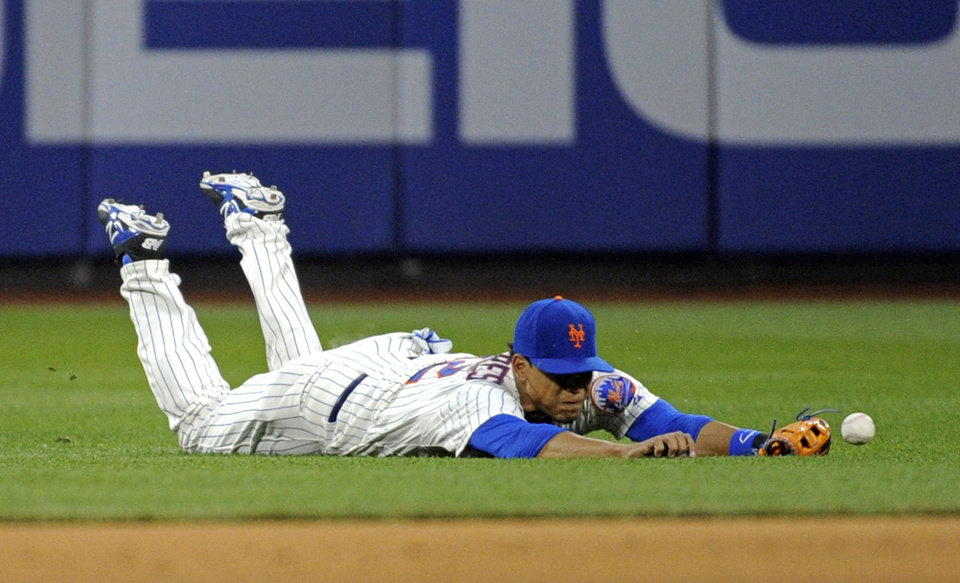Photo - New York Mets center fielder Juan Lagares cannot catch a ball hit by Philadelphia Phillie' Domonic Brown for an RBI-single during the first inning of a baseball game on Saturday, May 10, 2014, at Citi Field in New York. (AP Photo/Bill Kostroun)