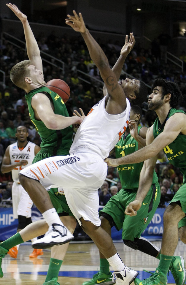 Photo - OSU's Marcus Smart loses the handle on the ball as Oregon's E.J. Singler and Arsalan Karzemi defend him in the second round of the NCAA Basketball tournament in San Jose, CA, Mar. 21, 2013. STEPHEN PINGRY/Tulsa World