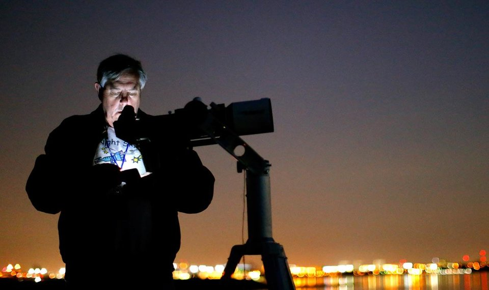 Photo -  Mike Brake checks a star map on his phone at Lake Hefner in Oklahoma City as he views the Pan-STARRS comet on Tuesday, March 12, 2013. Photo by Bryan Terry, The Oklahoman