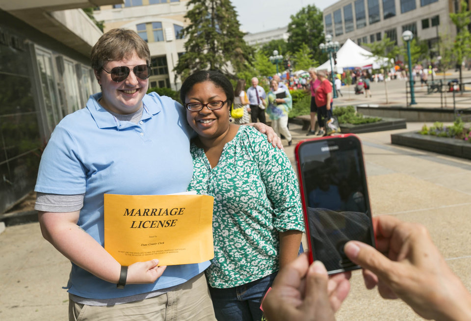 Photo - Meghan Connor, left, and Nujemi Champion, both of Madison, show off their wedding documents after getting married Saturday, June 7, 2014, in Madison, Wis. On Friday a federal judge struck down the state's gay marriage ban. (AP Photo/Andy Manis)