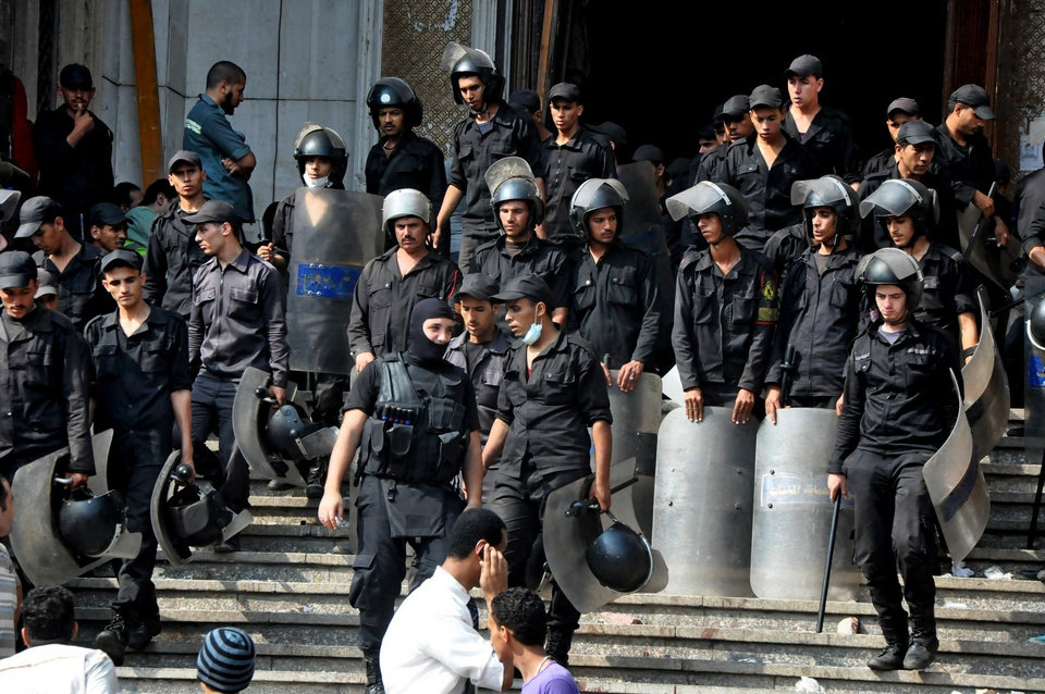 Photo - Egyptians security forces provide a cordon around the al-Fatah mosque, after hundreds of Muslim Brotherhood supporters barricaded themselves inside the mosque overnight, following a day of fierce street battles that left scores of people dead, near Ramses Square in downtown Cairo, Egypt, Saturday, Aug. 17, 2013. Authorities say police in Cairo are negotiating with people barricaded in a mosque and promising them safe passage if they leave. Muslim Brotherhood supporters of Egypt's ousted Islamist president are vowing to defy a state of emergency with new protests today, adding to the tension. (AP Photo/Hussein Tallal)