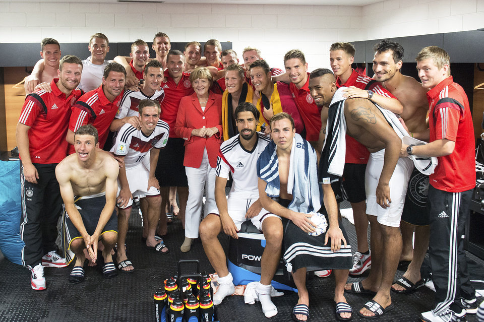 Photo - The photo provided German government shows German Chancellor Angela Merkel, center, posing for a photo with the German national soccer team after Germany won 4-0 in the group G World Cup soccer match between Germany and Portugal at the Arena Fonte Nova in Salvador, Brazil, Monday, June 16, 2014.  (AP Photo/Bundesregierun, Guido Bergmann)