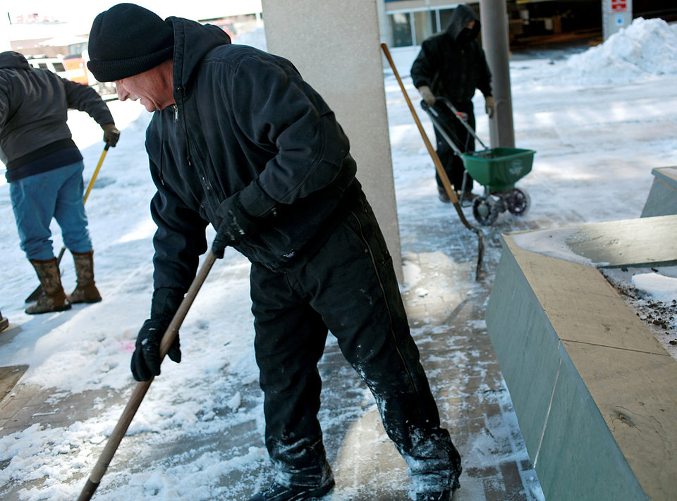 Photo - Lt. Steve Pence, of the Oklahoma County Sheriff's Department, (center) helps other county employees shovel ice and snow off the sidewalk in front of the Oklahoma County Office Building at Hudson and Robert S. Kerr in Oklahoma City on Wednesday, Feb. 2, 2011. Photo by John Clanton, The Oklahoman